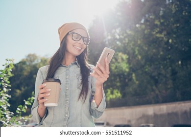 Portrait of beautiful hipster woman  reading message in the park