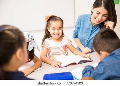 Portrait of a beautiful Hispanic preschool student enjoying her day at school and doing a writing exercise