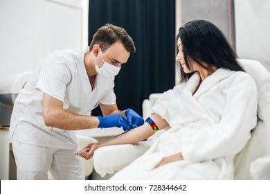 Portrait of a beautiful hispanic woman smiling while getting a blood test in a laboratory. Woman in a white coat gives blood in the clinic. A doctor is taking a blood test from a female patient.