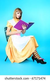 Portrait of a beautiful housewife reading a book. Studio shot.