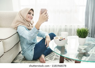 portrait of beautiful housewife wearing hijab taking selfies using mobilephone camera in a leisure time at home