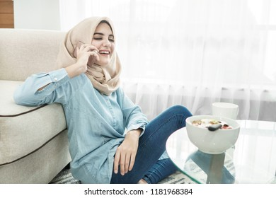 portrait of beautiful housewife wearing hijab talking on mobilephone while sitting relax in the morning at living room
