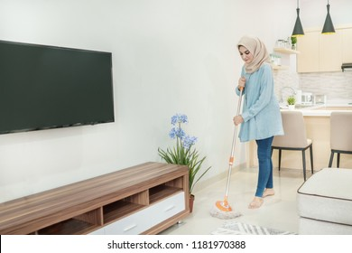 portrait of beautiful housewife wearing hijab cleaning her house