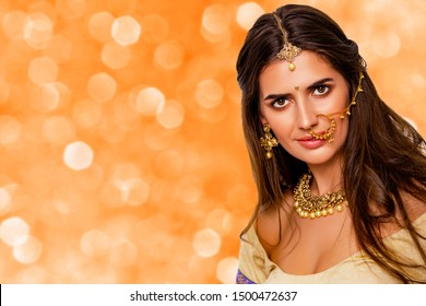 Portrait of beautiful indian girl. beauty portrait. isolated. orange background. Young hindu woman model with kundan jewelry set. Close up. Traditional India costume lehenga choli or sari. make-up