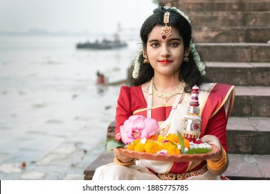Portrait of beautiful Indian girl in front of ganga river wearing traditional Indian saree, gold jewellery and bangles holding plate of religious offering. - Shutterstock ID 1885775785