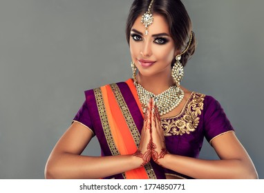 Portrait of a beautiful indian girl in a greetting pose to Namaste hands .India woman in traditional sari dress and jewelry.