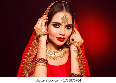 Portrait of beautiful indian girl in red bridal sari. Young hindu woman model with kundan jewelry set. Traditional Indian costume lehenga choli. Henna painting, mehendi on bride's hands.
