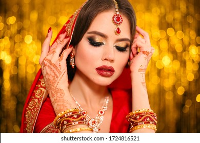 Portrait of beautiful indian girl in red bridal sari over golden bokeh. Young hindu woman model with kundan jewelry. Traditional Indian costume lehenga choli. Henna painting, mehendi on bride's hands.
