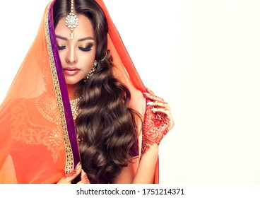 Portrait of beautiful indian girl in saree . Young India woman model  with tatoo mehndi  and kundan jewelry . Traditional  costume lehenga choli .