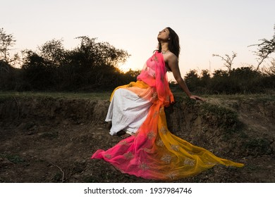 Portrait of beautiful Indian girl wearing Indian traditional dress. Young woman in traditional Indian costume lehenga choli with fashionable hairstyle poses