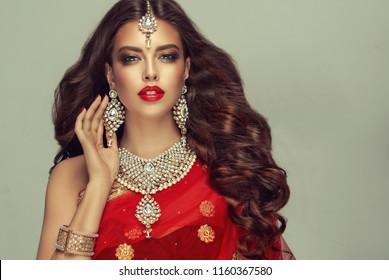 Portrait of beautiful indian girl. Young hindu woman model with kundan jewelry set. Traditional India costume red sari