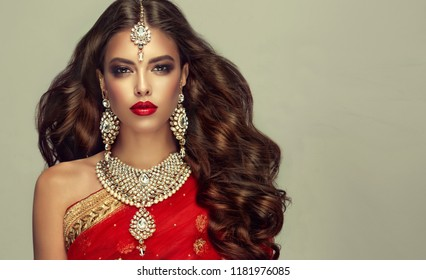 Portrait of beautiful indian girl. Young hindu woman model with kundan jewelry set. Traditional India costume red sari