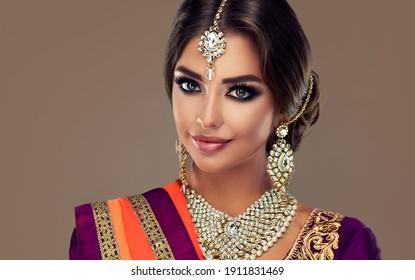Portrait of beautiful indian girl . Young hindu woman model  with tatoo mehndi  and kundan jewelry . Traditional Indian costume lehenga choli .