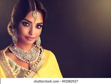 Portrait of beautiful indian girl . Young hindu woman model  with tatoo mehndi  and kundan jewelry . Traditional Indian costume  yellow saree