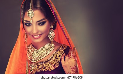 Portrait of beautiful indian girl. Young hindu woman model with tatoo mehndi  and kundan jewelry. Traditional Indian costume lehenga choli .