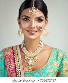 Portrait of beautiful indian girl. Young hindu woman model with kundan jewelry set. Traditional Indian costume lehenga choli or sari