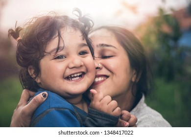 Portrait of a beautiful Indian mother with her cute little daughter with pleasure spending time together outdoor in nature, happy family life