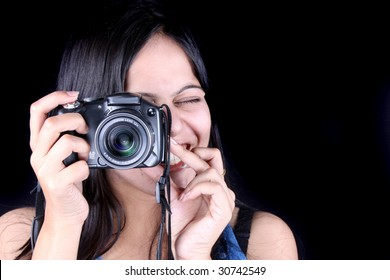 A portrait of a beautiful Indian woman with a camera, on black studio background.
