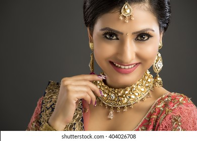 Portrait of beautiful Indian woman in glamorous outfit and jewelry with makeup in dark background.