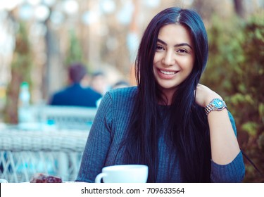 Portrait of a beautiful indian woman smiling outdoors on a terrace of a coffee shop restaurant
