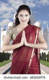 Portrait of a beautiful Indian woman wearing a red sari costume with Taj Mahal background