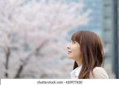 Portrait of beautiful Japanese business  woman  under a spring cherry blossom
