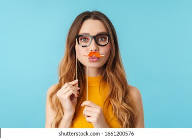 Portrait of beautiful joyous caucasian woman having fun while wearing paper eyeglasses and mustache isolated over blue background in studio