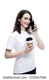 Portrait von einer wunderschönen, fröhlichen Kaukasierin, die eine Kaffeetasse hält und auf einem Handy unterhält, isoliert über blauem Hintergrund im Studio