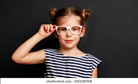 Portrait of beautiful kid putting on glasses on black background. Optometry and eye care concept.