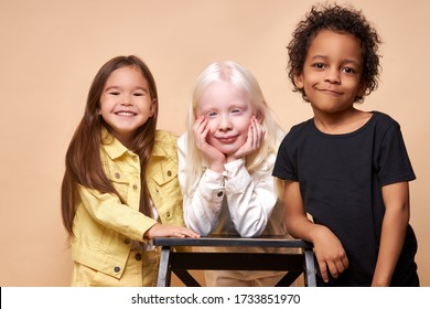 portrait of beautiful kids with natural unusual appearance. girl with albinism syndrome is friends with black african boy and american girl. children maintain tolerance and kindness to each other