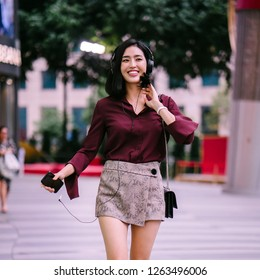 A portrait of a beautiful Korean woman in an elegant blouse and shorts dancing as she walks down a street in the city with her headphones on.