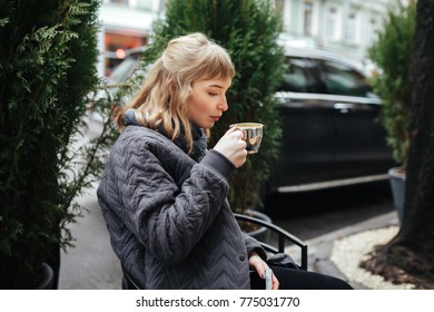 Portrait of beautiful lady with blond hair sitting and drinking coffee on city street isolated