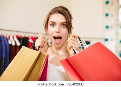 Portrait of beautiful lady with brown hair in pink pantsuit amazedly looking in camera while standing with shopping bags in hands in fashion boutique
