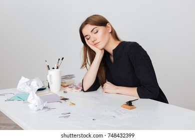 Portrait of beautiful lady sitting at the white desk and sleeping while leaning head on her hand isolated