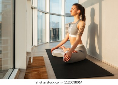 Portrait of beautiful lady in sporty top and leggings sitting in lotus pose and meditating on yoga mat while listening music in earphones at home isolated