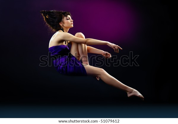 The portrait of a beautiful lady wearing a violet dress and zero gravity