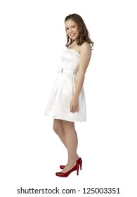 Portrait of beautiful lady wearing a white prom dress and red shoes smiling on a white background