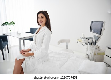 Portrait of beautiful lady in white soft bathrobe sitting on daybed. She is looking at camera and smiling