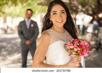 Portrait of a beautiful Latin bride with the groom standing behind her
