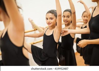 Portrait of a beautiful Latin girl enjoying her dance class among other girls and her teacher