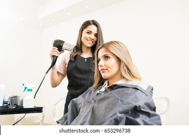 Portrait of a beautiful Latin hairstylist holding a blowdryer next to a customer in a hair salon