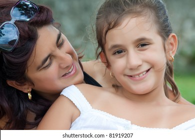 Portrait of a beautiful latin mother looking at her daughter