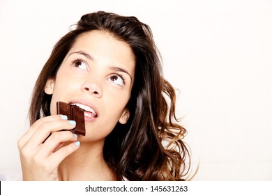 Portrait of a beautiful, latin Woman eating chocolate.