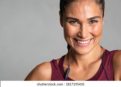 Portrait of beautiful latin woman smiling isolated on grey background. Close up face of sporty woman with big grin looking at camera on gray wall with copy space. Happy fit girl in sportswear laughing