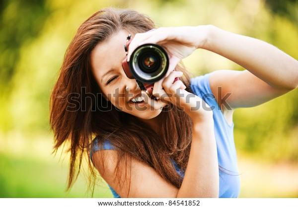 Portrait of beautiful laughing brunette girl wearing blue t-shirt, making photos at summer green park.