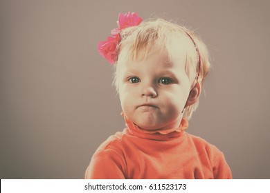 Portrait of a beautiful little blond girl on a gray background