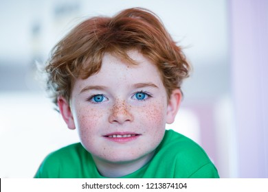 Portrait of a beautiful little boy, close-up happy kid, a child in a green T-shirt against the background of the room