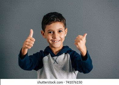 Portrait of beautiful little boy giving you thumbs up over gray background