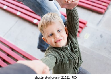 Portrait: a beautiful little boy looking up at his parents, holding hands