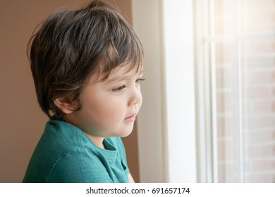 Portrait of beautiful little boy standing next to window and looking outside